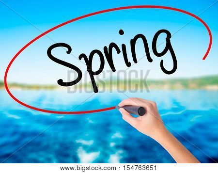Woman Hand Writing Spring With A Marker Over Transparent Board.