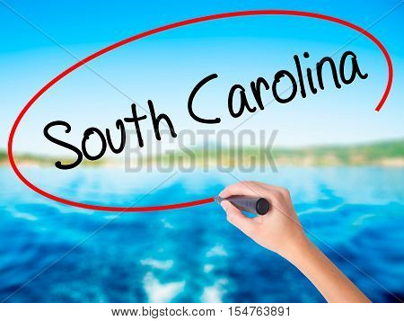 Woman Hand Writing South Carolina With A Marker Over Transparent Board.
