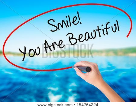 Woman Hand Writing Smile! You Are Beautiful With A Marker Over Transparent Board