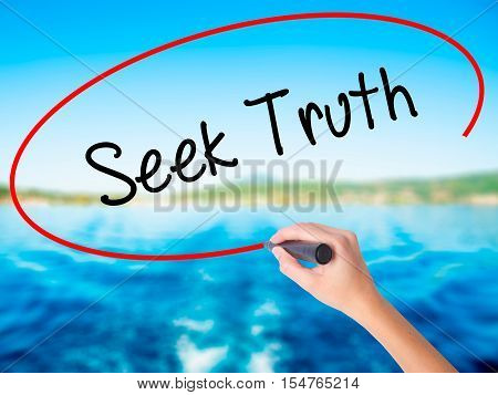 Woman Hand Writing Seek Truth With A Marker Over Transparent Board