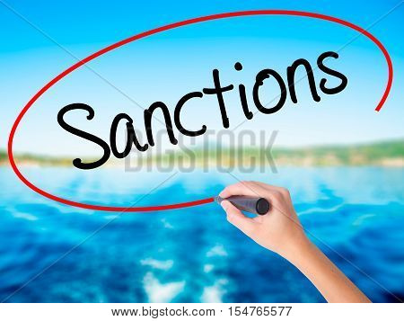 Woman Hand Writing Sanctions With A Marker Over Transparent Board.
