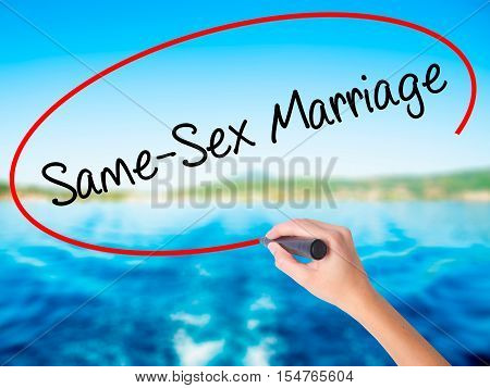 Woman Hand Writing Same-sex Marriage With A Marker Over Transparent Board
