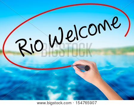 Woman Hand Writing Rio Welcome With A Marker Over Transparent Board.