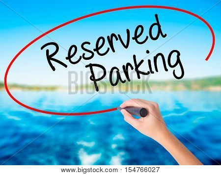 Woman Hand Writing Reserved Parking With A Marker Over Transparent Board
