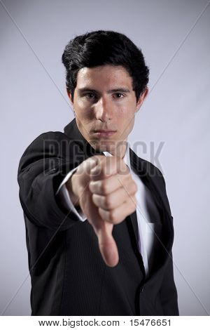 Businessman showing his rejection with his thumb down