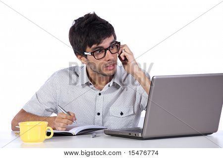 Young modern businessman talking on the phone and working with his laptop