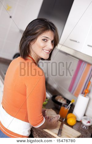 beautiful woman eating her breakfast and drinking her orange juice looking natural at her kitchen (selective focus with shallow DOF)
