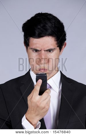 Businessman with a angry face expression looking to his mobile phone (isolated on gray)