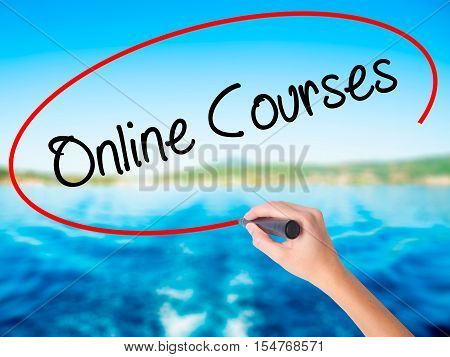 Woman Hand Writing Online Courses With A Marker Over Transparent Board