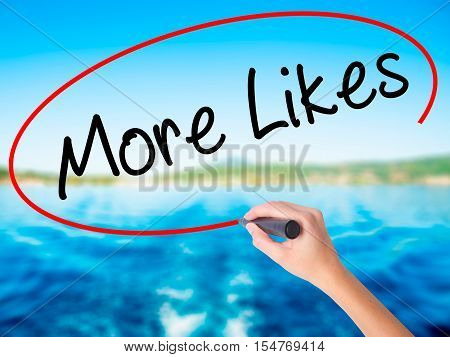 Woman Hand Writing More Likes With A Marker Over Transparent Board
