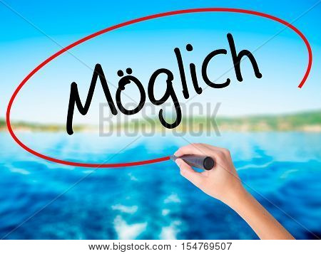 Woman Hand Writing Moglich (possible In German) With A Marker Over Transparent Board.
