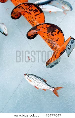 Fishing auger on ice of the frozen lake