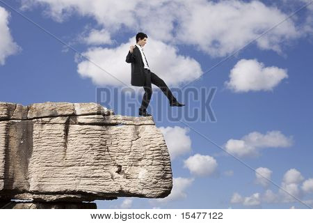Businessman making a danger and step falling from a rock