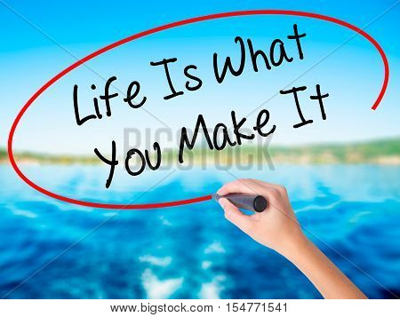 Woman Hand Writing Life Is What You Make It With A Marker Over Transparent Board