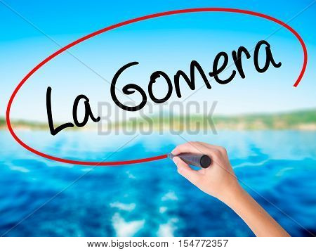 Woman Hand Writing La Gomera With A Marker Over Transparent Board.