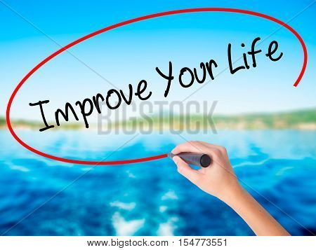 Woman Hand Writing Improve Your Life With A Marker Over Transparent Board.