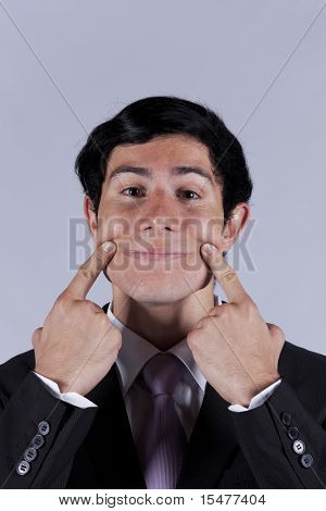 Young businessman with a funny face with a forced smile (isolated on gray)