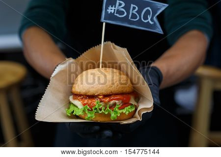 Fresh burger cooked at barbecue outdoors. Cookout american bbq food with text flag. Big hamburger with steak meat and vegetables closeup with chef unfocused at background. Street food, fast food.