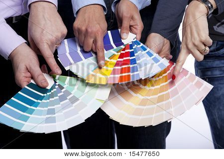 Group of people hands pointing to color samples in palette pantone (selective focus)