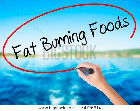 Woman Hand Writing Fat Burning Foods With A Marker Over Transparent Board
