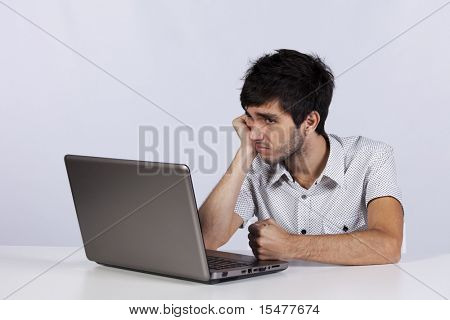 Young men working with his laptop with a bored face