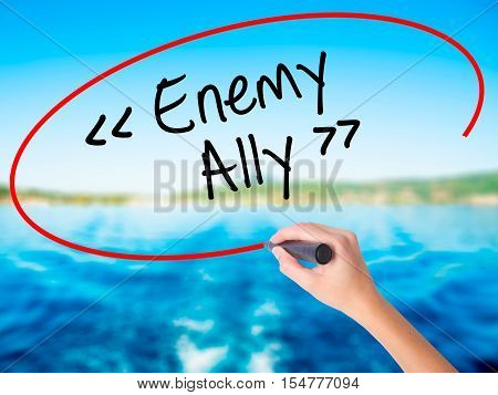 Woman Hand Writing Enemy - Ally With A Marker Over Transparent Board.