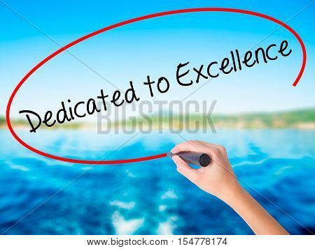 Woman Hand Writing Dedicated To Excellence  With A Marker Over Transparent Board