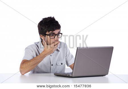 junger Mann schockiert mit etwas, das er auf seinem Laptopcomputer zu sehen