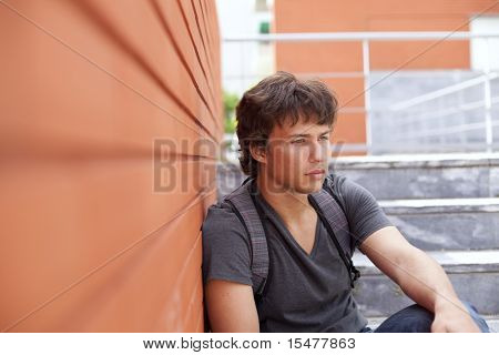 handsome teenager next to a red brick wall (selective focus)