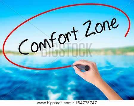 Woman Hand Writing Comfort Zone With A Marker Over Transparent Board