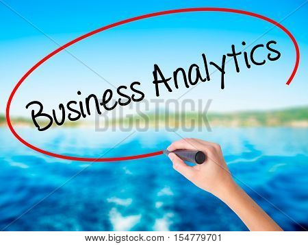 Woman Hand Writing Business Analytics With A Marker Over Transparent Board