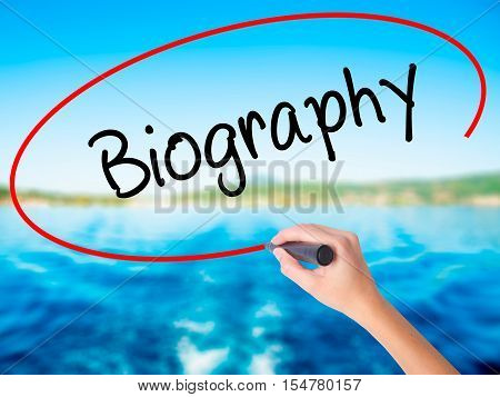 Woman Hand Writing Biography  With A Marker Over Transparent Board