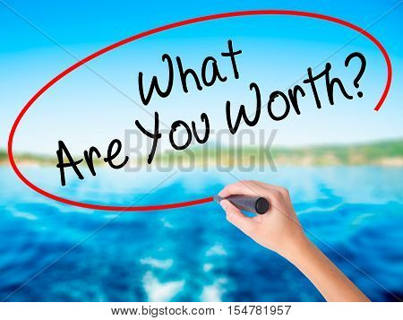 Woman Hand Writing What Are You Worth? With A Marker Over Transparent Board
