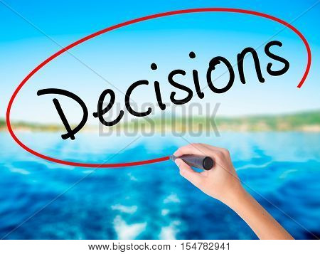 Woman Hand Writing Decisions With A Marker Over Transparent Board