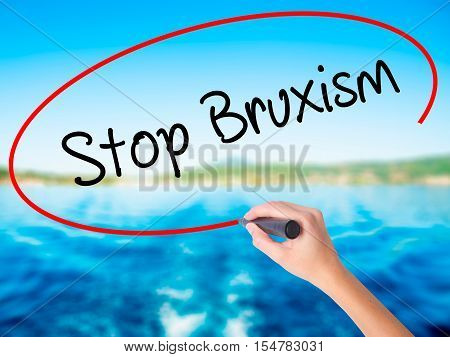 Woman Hand Writing Stop Bruxism With A Marker Over Transparent Board