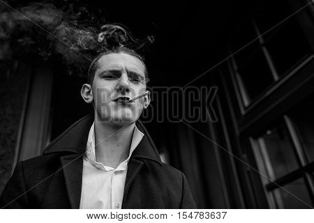 Serious young man standing and beautifully smokes