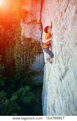 male rock climber. rock climber climbs on a rocky wall. man makes hard move