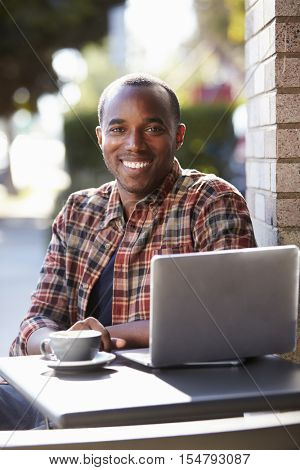 Young black man with laptop outside a cafe looking to camera