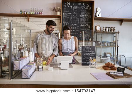 Couple working together at the till in a coffee shop