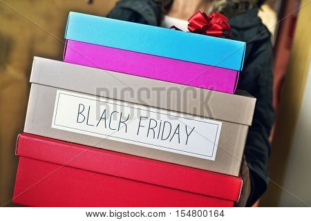 closeup of a young caucasian man holding a pile of boxes, one of them with the text black friday written in it