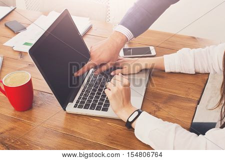 Closeup of businessman's hand supervising his assistant's work on the laptop computer. Man helps woman in the office, unrecognizable people. Boss checking secretary's job execution, point at screen