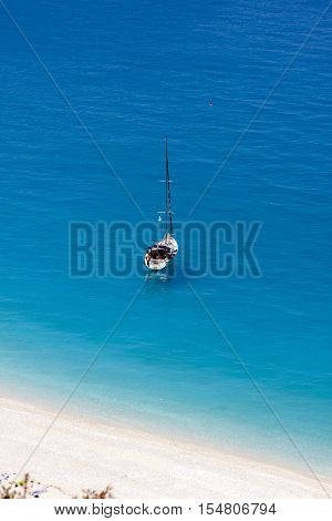 A sailboat in the sea of the famous Myrthos Bay in Kefalonia, Greece