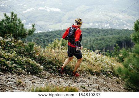 Yalta Russia - October 5 2016: male athlete marathon runner running with mountains along trail during Crimea mountain marathon