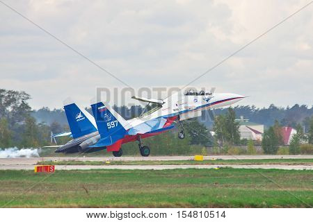 Kiev Region Ukraine - October 2 2010: Sukhoi Su-30LL fighter plane in Russian flag colors is landing with smoke on the runway holding the nose up