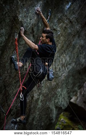 Extreme sport climbing. Young male rock climber on a rock wall.