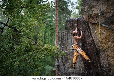 Extreme sport climbing. Young male rock climber reaching the top of a rock.