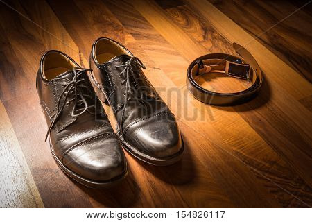 Stylish Black Handcrafted Dress Shoes And Leather Belt On Wooden Floor Spotlight Sun Clothing