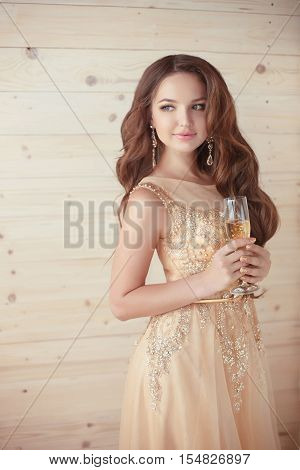 Party, Drinks. Beautiful Elegant Woman In Evening Dress With Glass Of Sparkling Wine Over Beige Wood