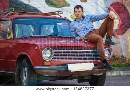 Confident wealthy young man near old car
