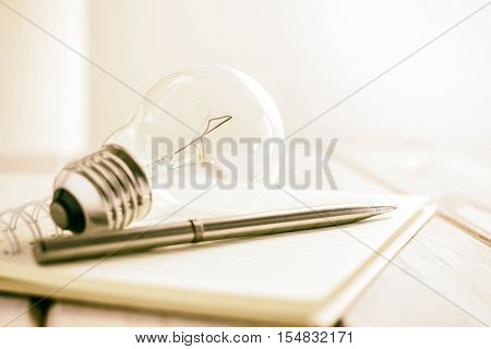 closeup pen on notebook with light bulb creative writing concept.